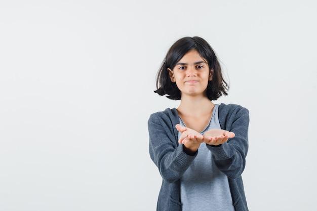 Молодая девушка протягивает руки к камере, когда получает что-то в светло-серой футболке и темно-серой толстовке с капюшоном на молнии и выглядит мило.