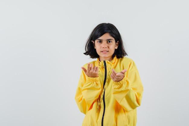 Молодая девушка протягивает руки к камере, приглашает прийти в желтом бомбардировке и выглядит счастливой.