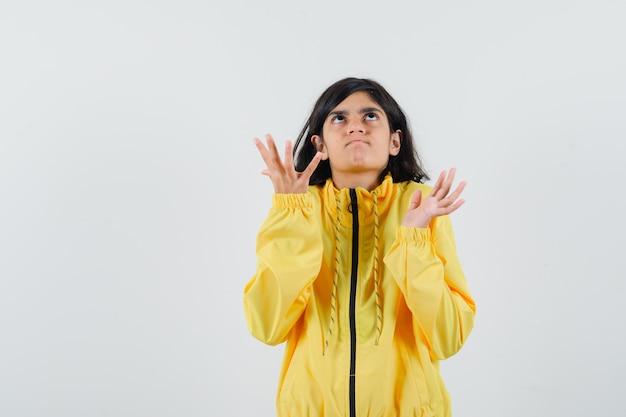 Молодая девушка протягивает руки вверх в желтой куртке-бомбардировщике и выглядит сердитой