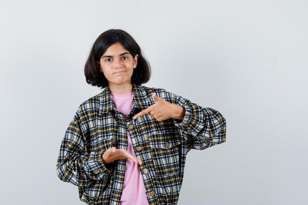 어린 소녀는 한 손으로 무언가를 잡고 체크 셔츠와 분홍색 티셔츠를 입은 검지로 그것을 가리키며 귀엽고 앞모습을 보고 있습니다.