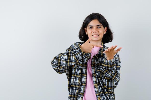 어린 소녀는 한 손으로 무언가를 잡고 체크 셔츠와 분홍색 티셔츠를 입고 검지 손가락으로 그것을 가리키며 예쁘게 보이고 앞모습을 보고 있습니다.