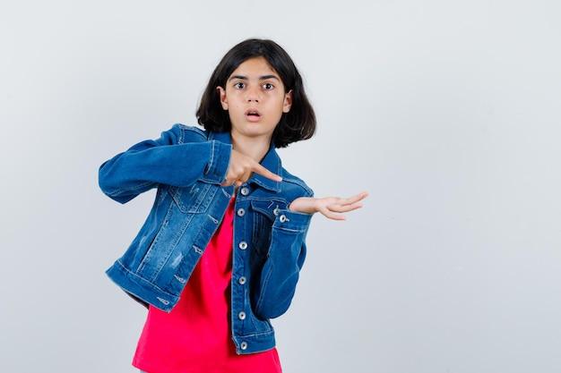 어린 소녀는 한 손으로 무언가를 잡고 빨간 티셔츠와 진 재킷을 입은 검지로 그것을 가리키며 놀란 표정을 짓고 있습니다. 전면보기.