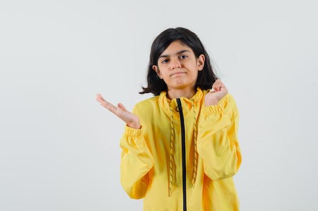 Молодая девушка протягивает руку влево, сжимает кулак в желтом бомбере и выглядит серьезной.