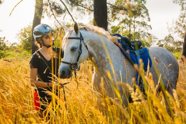 森の中の日没の下で白い馬をなでる少女