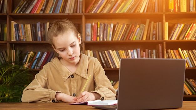 Young girl student in brown jacket writes lecture into paper notebook with pencil in left hand at laptop against large wooden bookcase in library