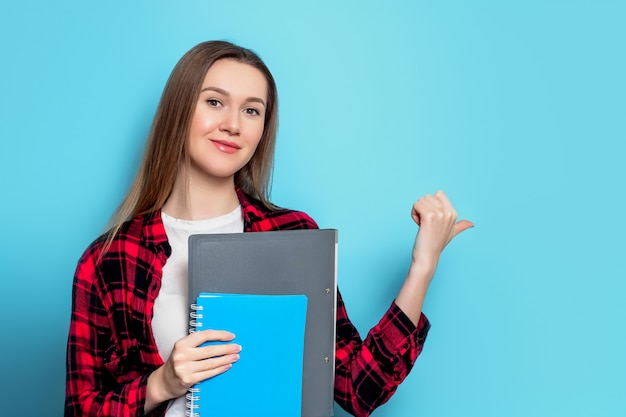 Young girl student in a checkered red shirt and white t-shirt with notebook and folder points a finger at the wall. student girl pointing finger on  isolated on blue wall