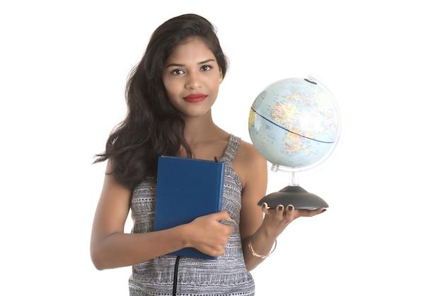 Студент маленькой девочки держа книгу с глобусом на белой стене. образование в концепции колледжа средней школы университета
