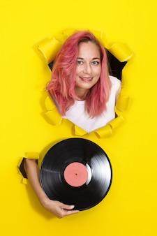 노란색 종이 벽에 찢어진 된 구멍을 통해 비닐 레코드를 들고 젊은 여자 학생. 최소한의 복고풍 컨셉