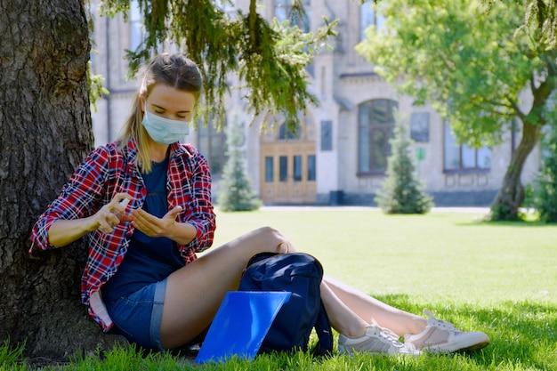 防護マスクの若い女子学生は大学近くの木の下に座って、防腐剤で手を消毒します。 covid-19パンデミックの後に学校に戻る。新しい正常。