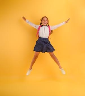 어린 소녀 학생이 노란색에 우등으로 승진을 위해 행복하게 점프합니다.