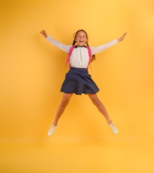 Young girl student jumps high happy for the promotion with honors on yellow