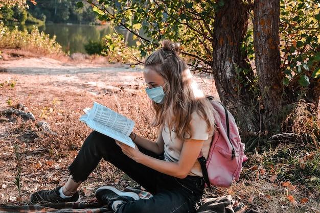 어린 소녀, 배낭을 메고 야외에 앉아 책을 읽는 학생. 보호용 안면 마스크 착용. 집에서 공부하세요. 코티지코어. naturecore, 자연 애호가. 학교로 돌아가다