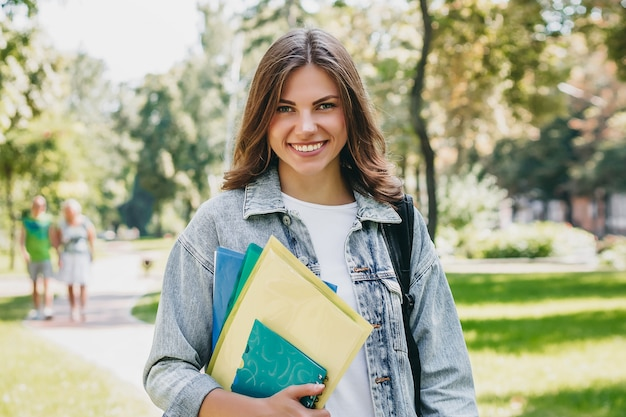 Young girl student smiling in the park. cute girl student holds folders and notebooks in hands. learning, education concept