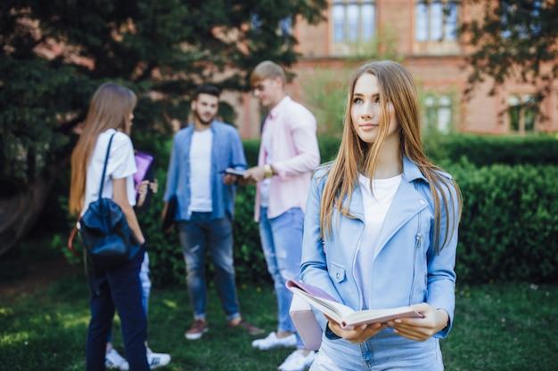 캠퍼스와 미소에 서 있는 어린 소녀 학생.