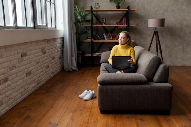 Студент молодой девушки учится в гостиной, сидя на диване и используя наушники и ноутбук.