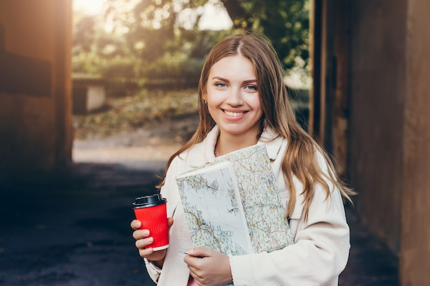 A young girl student walks around the city with a map and holds a cup of coffee.