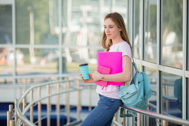 Young girl student with a cup of coffee on the street