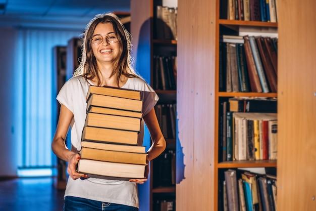 笑みを浮かべて図書館で眼鏡をかけた若い女子学生と書籍のスタックを運ぶ。試験準備
