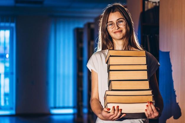 図書館笑顔で眼鏡の若い女子学生と書籍のスタックを運ぶ。試験準備