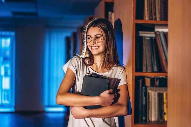 Young girl student with glasses in library stands near bookshelves. girl smiles and holds a book in her hands. exam preparation