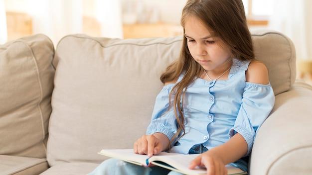 Молодая девушка учится дома на диване с копией пространства