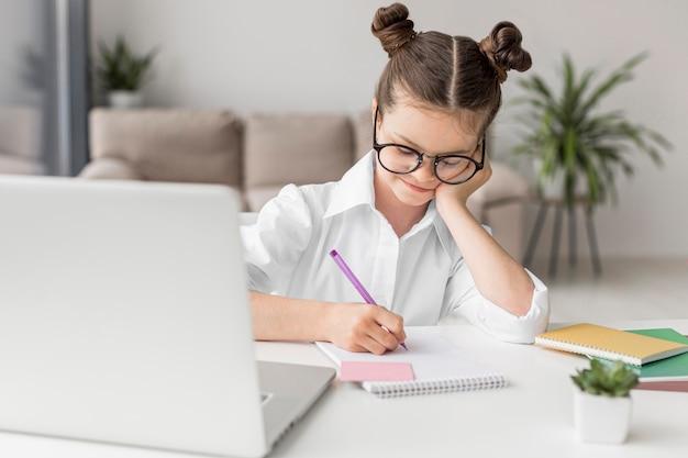 Молодая девушка учится на ноутбуке