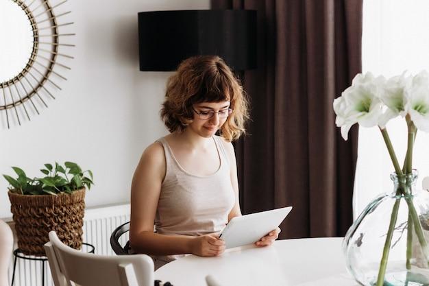 Молодая девушка учится онлайн. домашнее образование и домашнее обучение. онлайн-уроки на цифровом планшете