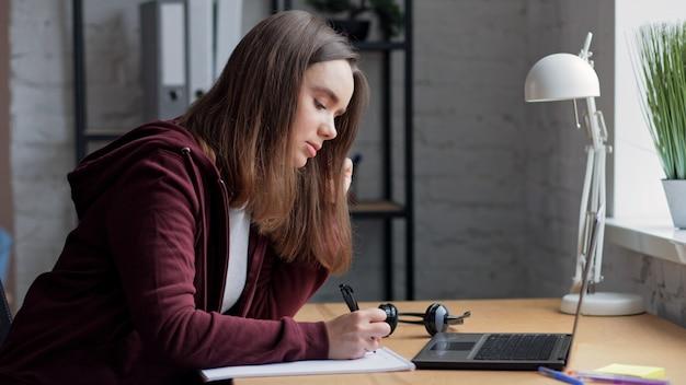 Молодая девушка учится онлайн с помощью веб-камеры ноутбука, писать лекцию в ноутбуке.