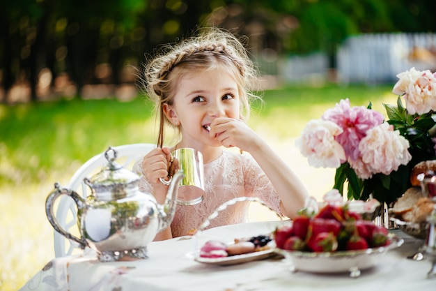 The young girl in the summer park at a beautiful table. tea