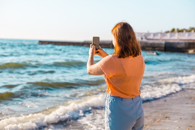 A young girl in a summer t-shirt and shorts makes a photo of the sea or ocean on the shore on sunny day