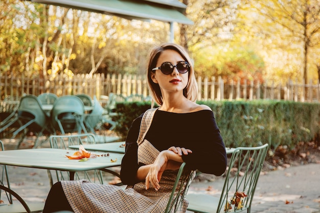 Young girl in sunglasses sitting chair in cafe