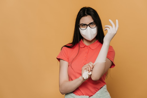 Young girl in surgical mask and glasses, wearing in a pink t-shirt, putting on protective gloves, looks confident, protection against coronavirus pandemic, quarantine at home. covid-19 concept.