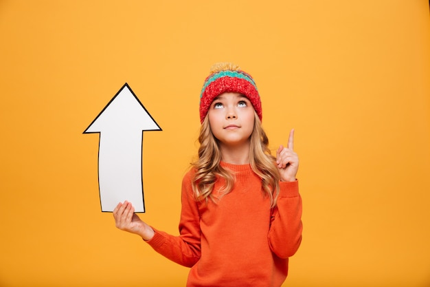 Young girl in sweater and hat holding paper arrow while pointing and looking up over orange