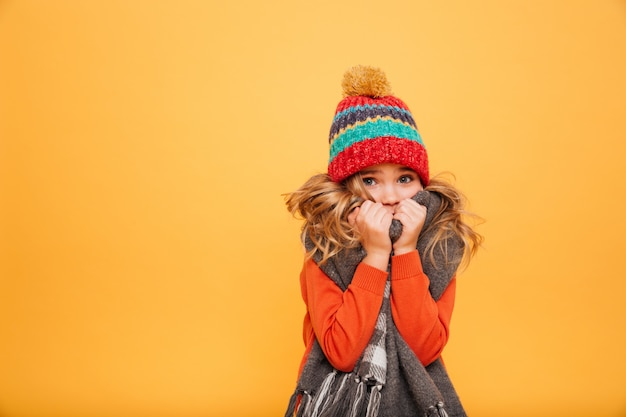 Young girl in sweater, scarf and hat having cold while looking at the camera over orange