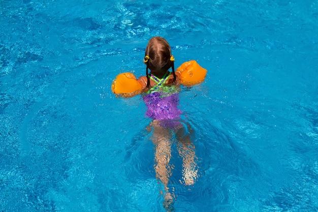 수영장에서 수영하는 어린 소녀.