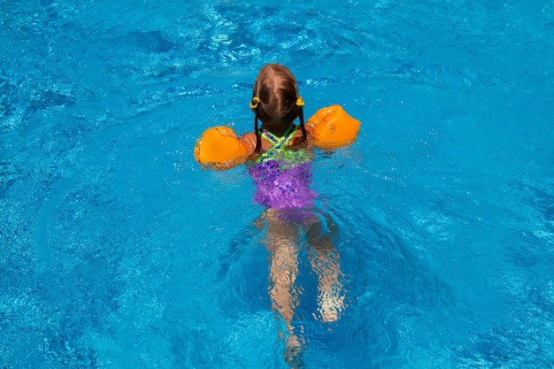 Young girl swiming in the pool.