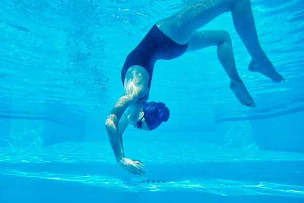 Young girl swimmer in swimsuit with goggles and swimming cap underwater in pool