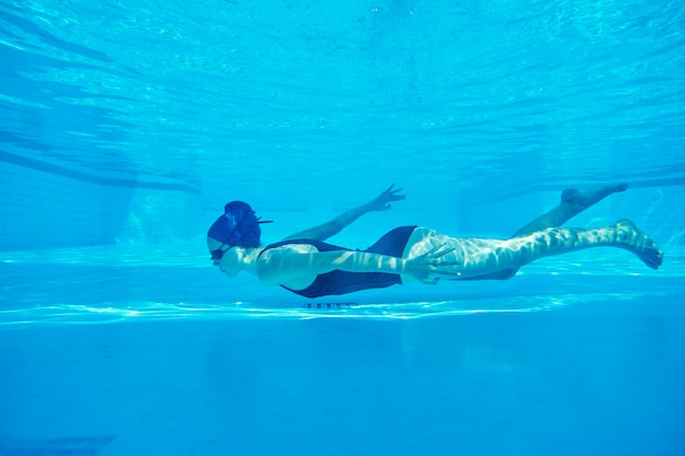 Young girl swimmer underwater in pool
