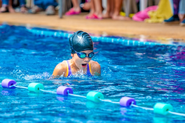 Young girl swimmers practicing lap swimming