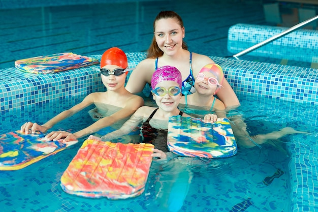 Young girl swimming instructor with children in the pool