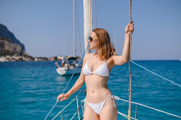 Young girl in a swimsuit on a luxury yacht summer vacation at sea