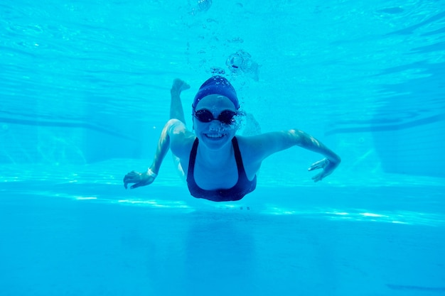 Young girl in swimsuit with goggles and swimming cap swimming underwater