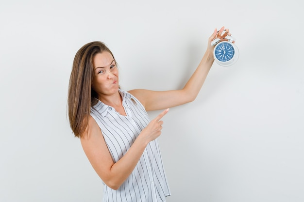 Young girl in t-shirt pointing at alarm clock and looking doubtful , front view.