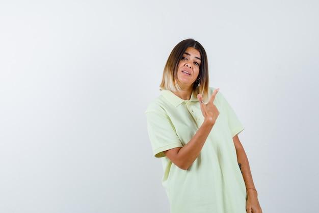 Giovane ragazza in t-shirt rivolto in alto a destra con il dito indice e guardando fiducioso, vista frontale.