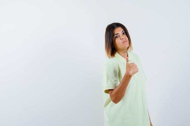 Giovane ragazza in t-shirt che mostra il pollice in alto e guardando fiducioso, vista frontale.