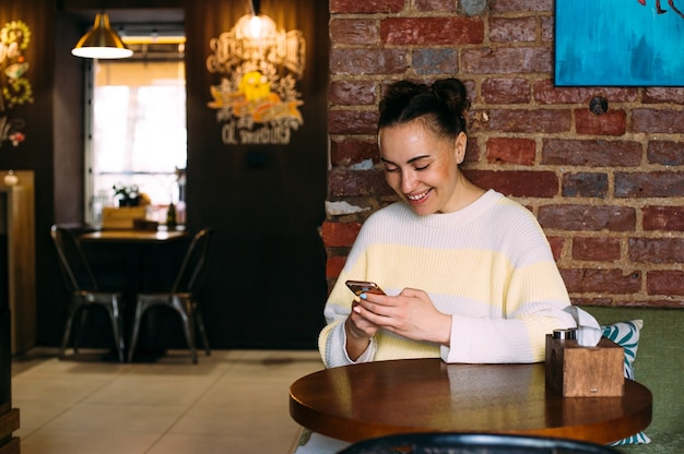 A young girl at a table in a cafe looks at the phone smiles and texting