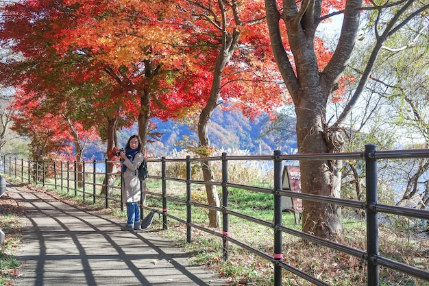 Young girl take photo  in autumn red maple leaves