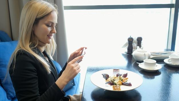 어린 소녀는 카페에서 현대적인 스마트폰으로 음식 사진을 찍습니다.