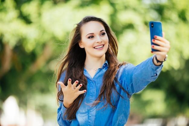 若い女の子は夏の街の通りで携帯電話で手から自分撮りを取ります。アーバンライフコンセプト。