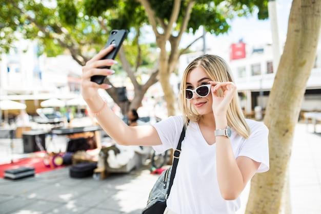 若い女の子は夏の街の通りで携帯電話で手から自分撮りを取ります。